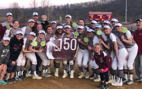 The softball team gathering for a picture to celebrate Kate Rittenbaugh's 150 hits.