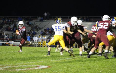 Quarterback, Josh Leininger, scrambles out of the pocket to try and get his pass off to one of his receivers.