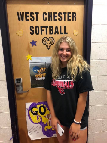 Trisha Kopinetz stands in front of her college softball team's dorm room.