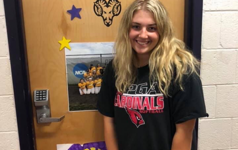 Trisha Kopinetz stands in front of her college softball team's dorm room.