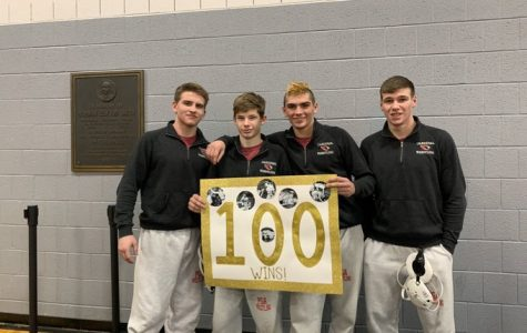 The senior wrestlers posing with Travis' 100th win poster after the match. From left to right: Gavin Harris, Travis Anderson, Chris Charles, Caleb Reiter.