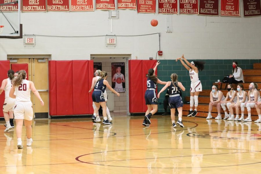 Mikaili Donmoyer shoots a three over two defenders.