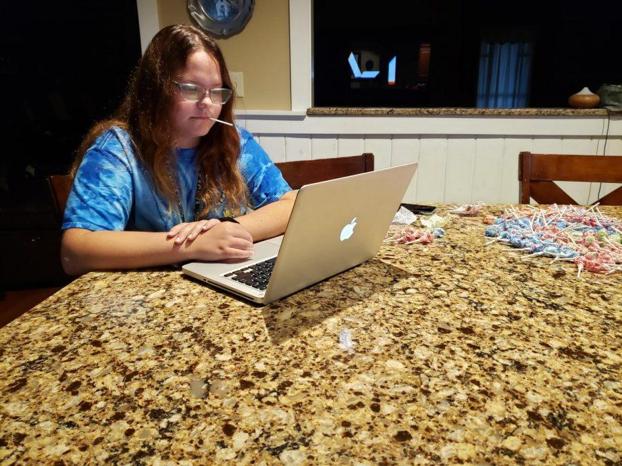 Senior Alexa Schlein enjoys a lollipop while watching videos on math on her computer.