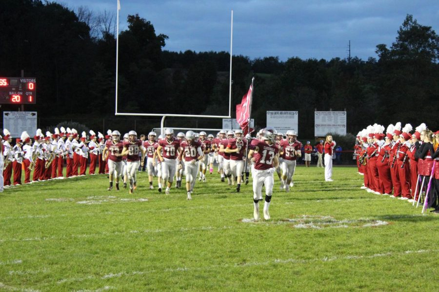 The Cardinal Football team running onto the field at the beginning of the game.