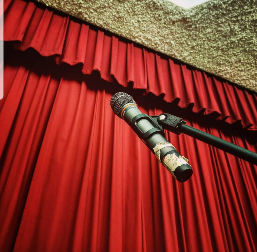 A microphone in front of the stage in preparation of the musical practice.