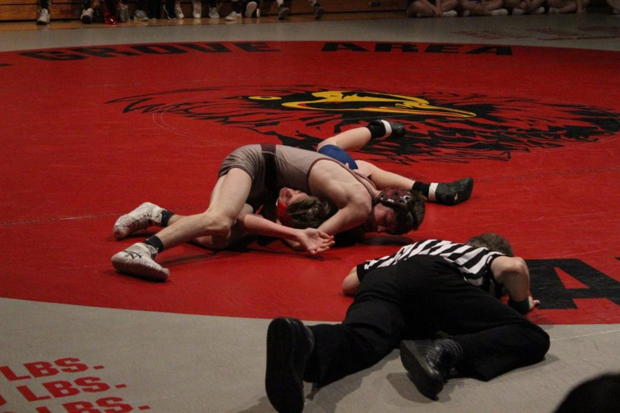 As Travis Anderson attempts to pin his opponent, the referee looks to see if the Jim Thorpe wrestler is pinned.