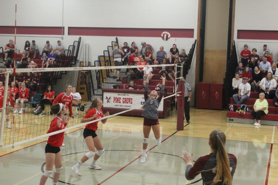 Alera August sets the volleyball for her teammate to spike.
