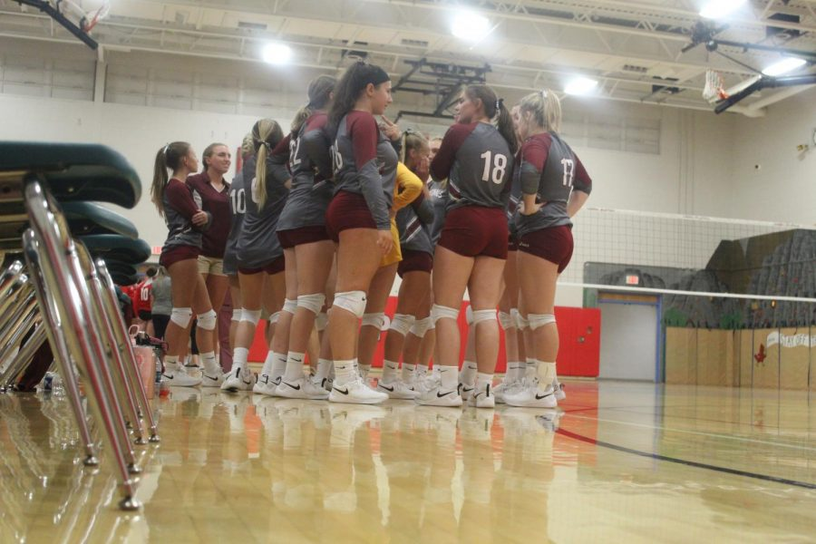 Volleyball team discussing something in the huddle.