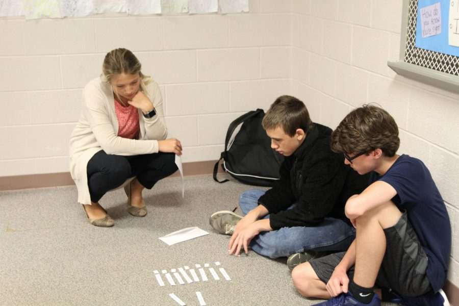Miss Deegan helping students on class assignment.