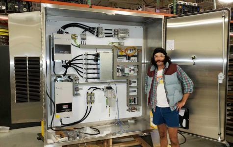 Bettinger standing next to an electrical control panel that he helped design and build.