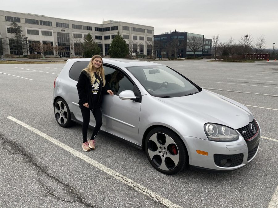 Lindsey Kemmerling standing next to her first car. It is a 2008 Volkswagen GTI.