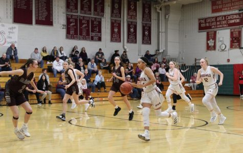 Mikaili Donmoyer dribbling the ball down the court, attempting to keep the ball away from her opponents.