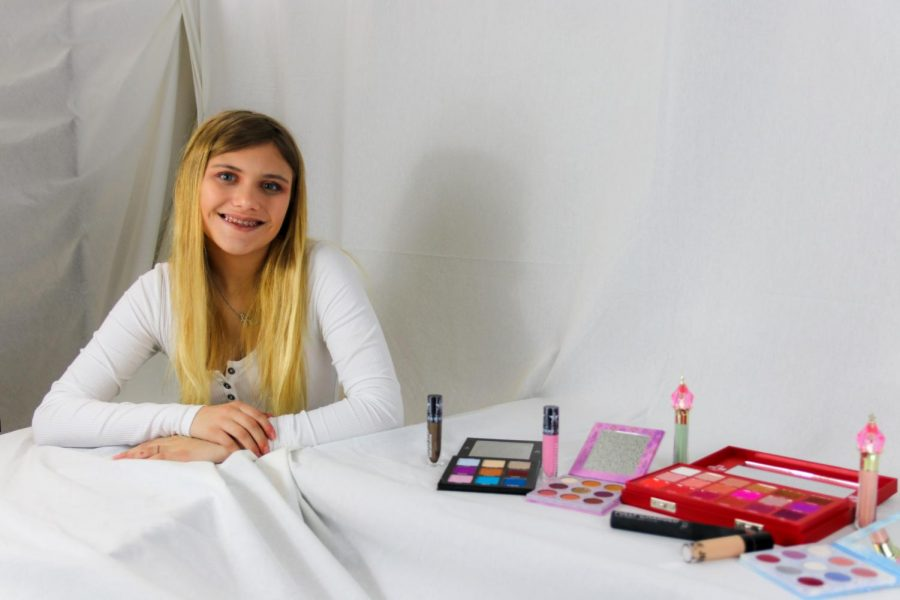 Lindsey Kemmerling posing with some of her makeup collection. Products used for her look include Urban Decay Stay Naked foundation, color correctors by Jeffree Star Cosmetics, concealer by Kylie Cosmetics,