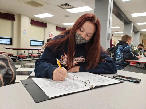 Sophomore Lilly Barra is rushing to complete homework before her next class period in the lunch room.