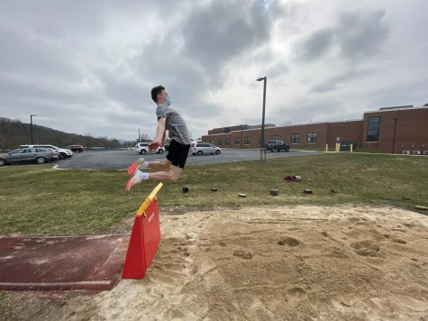 A photo of Josh Leininger, senior, practicing his long jump form.