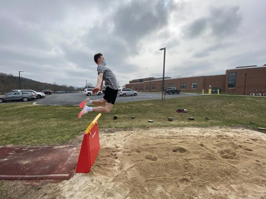 A photo of Josh Leininger, senior, practicing his long jump form.